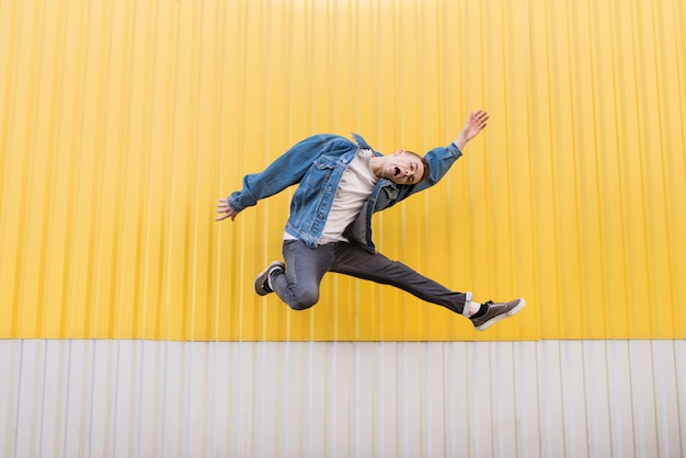 Szalony młody człowiek w dżinsowej kurtce skacze na tle żółtej ściany