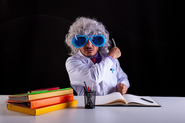Szalony nauczyciel nauk ścisłych w białym fartuchu z rozczochranymi włosami w śmiesznych okularach siedzący przy biurku trzymający różdżkę wskazującą na tablicę