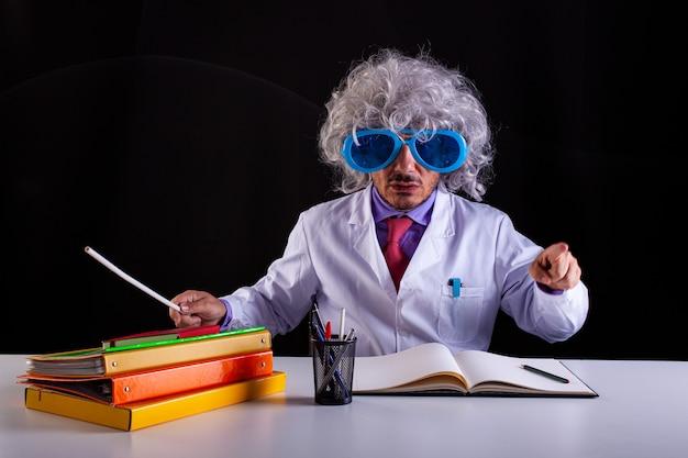 Szalony nauczyciel nauk ścisłych w białym fartuchu z rozczochranymi włosami w śmiesznych okularach siedzący przy biurku