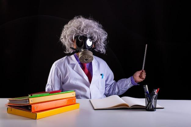 Szalony nauczyciel przedmiotów ścisłych w białym fartuchu z rozczochranymi włosami siedzący przy biurku nosi maskę gazową
