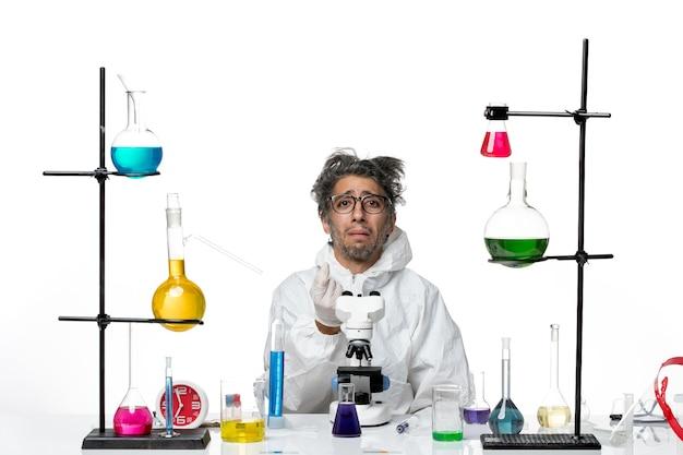 Szalony naukowiec mężczyzna z widokiem z przodu w specjalnym kombinezonie ochronnym, siedzący wokół stołu z roztworami na jasnobiałym tle choroby, wirusa laboratoryjnego