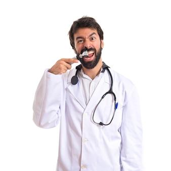 Szalony otorhinolaryngologist z otoscope nad białym tłem