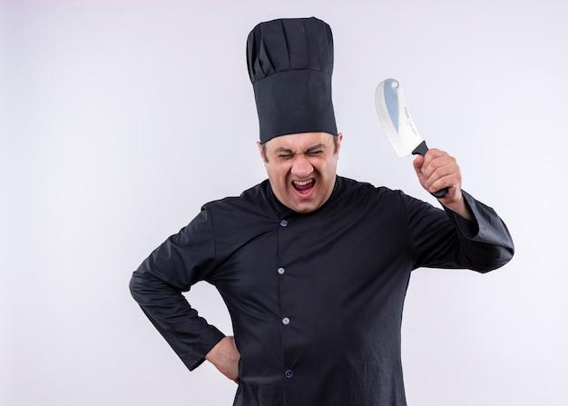 Szalony szalony kucharz mężczyzna ubrany w czarny mundur i kapelusz kucharza machający nożem, krzycząc z wściekłą twarzą stojącą na białym tle