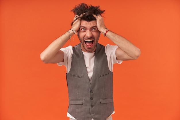 Szalony, szalony młody z włosiem i włosami stojącymi, trzyma ręce na głowie, krzyczy i patrzy w kamerę