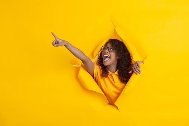 Szalony szczęśliwy wskazujący. wesoła afro-młoda kobieta w rozdartym tle żółtego papieru, emocjonalna, ekspresyjna. przełamanie, przełom. pojęcie ludzkich emocji, wyraz twarzy, sprzedaż, reklama.