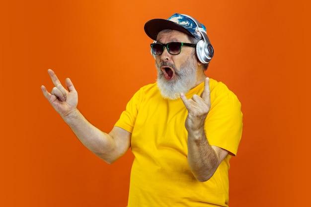 Szalony taniec. portret starszego hipster człowieka za pomocą urządzeń, gadżetów na białym tle na pomarańczowym tle studio. koncepcja tech i radosny starszy styl życia. modne kolory, wieczna młodość. miejsce na reklamę.