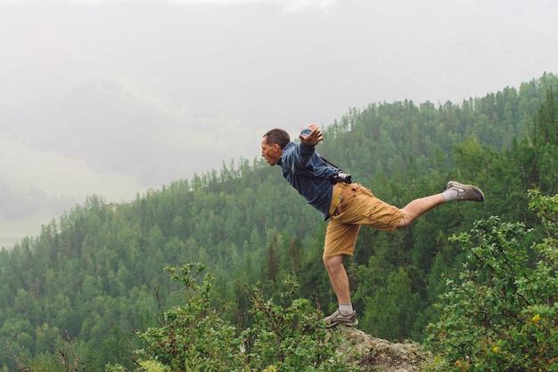 Szalony turysta na szczycie góry.