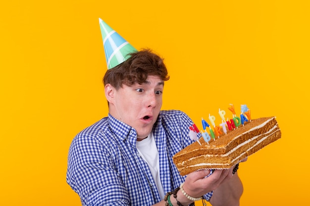 Szalony wesoły młody człowiek w papierowym gratulacyjnym kapeluszu trzyma ciasta wszystkiego najlepszego z okazji urodzin stojąc na żółtej ścianie. koncepcja jubileuszowe gratulacje.