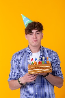 Szalony wesoły młody człowiek w papierowym gratulacyjnym kapeluszu, trzymając ciasta wszystkiego najlepszego z okazji urodzin stojących na