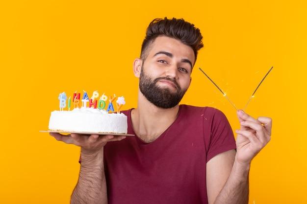 Szalony wesoły młody facet trzyma płonącą świecę w dłoniach i gratulacyjne domowe ciasto na żółtym tle. koncepcja obchody urodzin i rocznicy.