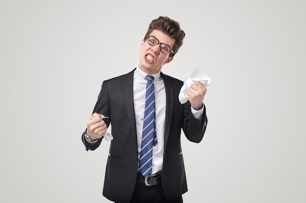 Szalony wściekły młody biznesmen w formalnym garniturze i okularach zdziera arkusz papieru ze złością na białym tle