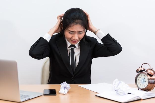 Szalony wściekły młody bizneswoman na biurku.