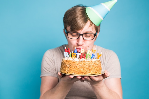 Szalony zabawny młody człowiek w okularach i papierowych gratulacyjnych kapeluszach, trzymając ciasta szczęśliwy urodziny stojący