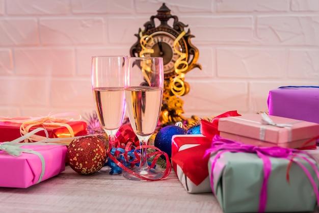 Szampan w kieliszkach na drewnianym stole z kolorowymi prezentami świątecznymi