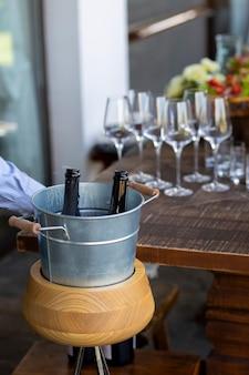 Szampan w wiaderku z lodem. butelka otwartego szampana. z butli wydobywa się gaz. szampan jest otwarty. koncepcja wakacje. strona. ślub.