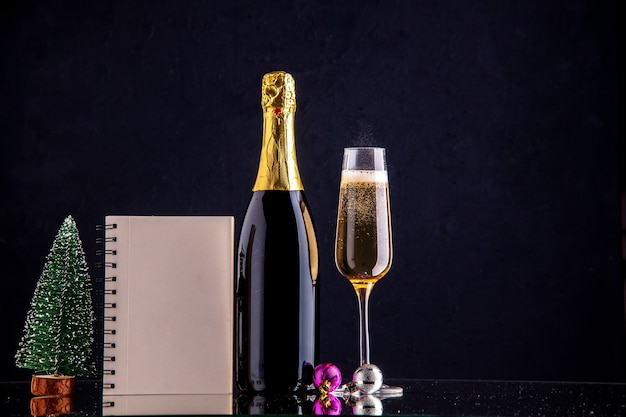 Szampan z widokiem z przodu w butelce i szklanym mini notatniku świątecznym na ciemnej powierzchni