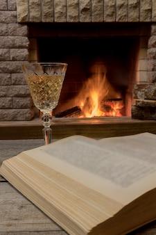 Szampańskie szkło i otwarta książka na przytulnym kominku.