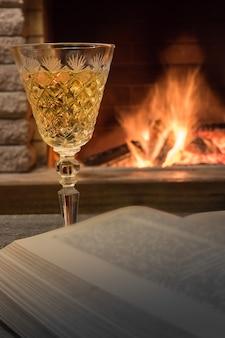 Szampańskie szkło i otwarta książka o przytulnym kominku.