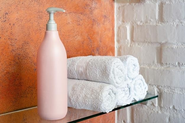 Szampon balsam mydło butelka produktu kosmetycznego do pielęgnacji włosów, higieny ciała i rolek ręczników na półce w łazience.spa pielęgnacja włosów, usługi kosmetyczne i zdrowotne dla kobiet.
