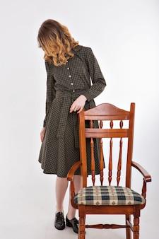 Szampon reklamowy, do farbowania włosów. śliczna kobieta. dziewczyna w stylu retro w pobliżu krzesło.