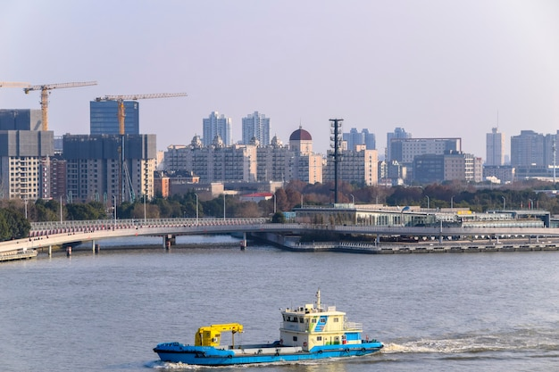 Szanghaj, chiny - 18 lutego 2021: rzeka huangpu w szanghaju, chiny ze statkiem przewożącym towary. w tle nowoczesne drapacze bundu.