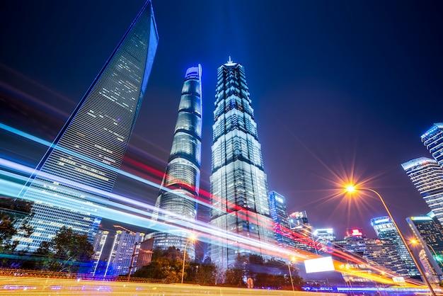 Szanghaj miasta budynki przy nocą i zamazanymi samochodowymi światłami