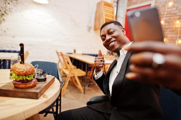 Szanowany młody człowiek w czarnym garniturze siedzi w restauracji i robi selfie przeciwko smacznemu podwójnemu burgerowi i pokazuje kciuk do góry