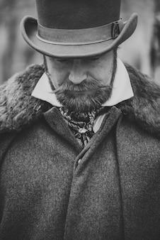 Szanowany wąsaty mężczyzna w klasycznym stroju, płaszczu i kapeluszu w stylu retro.