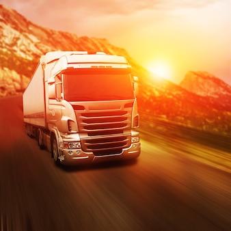 Szara ciężarówka na autostradzie o zachodzie słońca