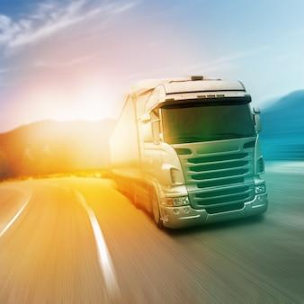 Szara ciężarówka na autostradzie w słońcu