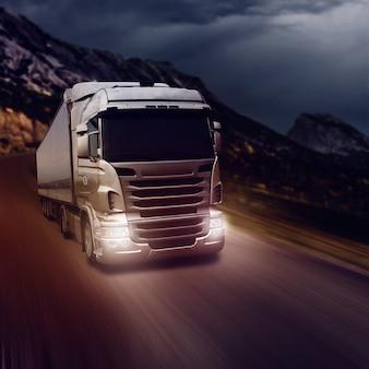 Szara ciężarówka na drodze autostrady w nocy