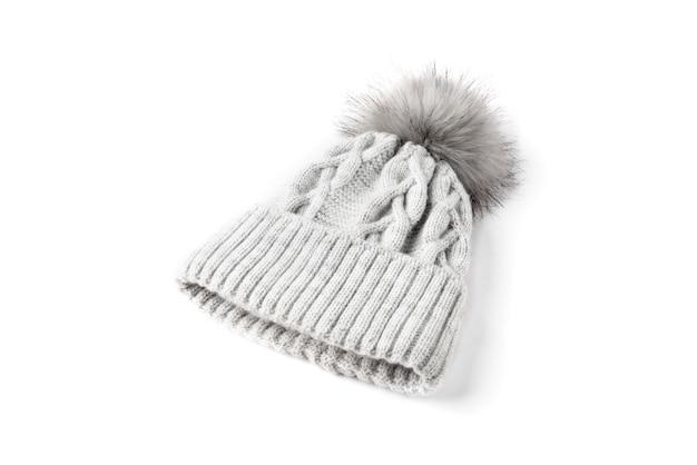 Szara czapka zimowa z dzianiny z boomem na białym tle.
