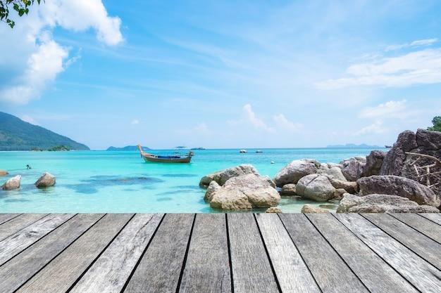 Szara deska drewniana na krystalicznie czystym morzu z łodzią z długim ogonem na wyspie lipe