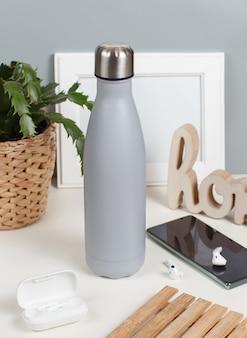 Szara izolowana butelka na białym biurku otoczona nowoczesnymi gadżetami i widokiem roślin z przodu