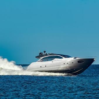 Szara łódź motorowa szybko płynie nad rzeką na łotwie. sport wodny