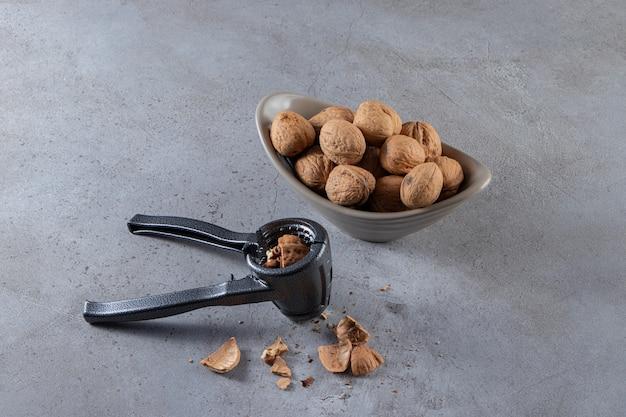 Szara miska organicznych łuskanych orzechów włoskich i łupania orzechów na kamiennym stole.