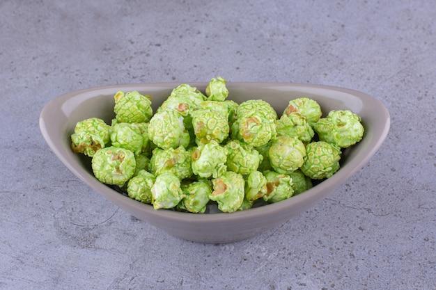 Szara miska owalna z pysznym popcornem pokrytym cukierkami na marmurowym tle. zdjęcie wysokiej jakości