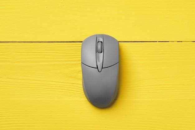 Szara mysz komputerowa na żółtym tle widok z góry