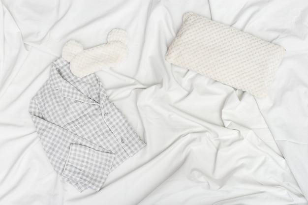 Szara piżama, maska do spania, miękka puszysta poduszka na białym zmiętym prześcieradle