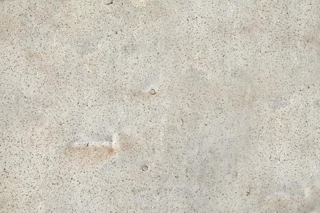 Szara powierzchnia betonu z mikropęknięciami, małymi otworami i wtrąceniami piasku.