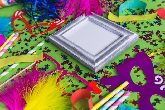 Szara ramka z konfetti, kolorowe okulary i kije