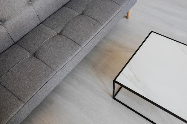 Szara rozkładana sofa przy marmurowym stole