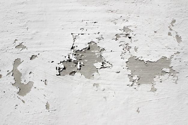 Szara ściana z łuszczącą się szarą farbą stara odrapana szara betonowa ściana z poważnymi uszkodzeniami chropowata powierzchnia teks...