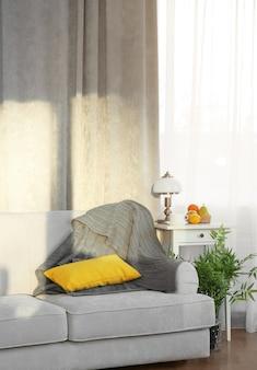 Szara sofa, mały stolik i zielona roślina na zasłonie