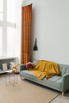Szara sofa w salonie w skandynawskim minimalistycznym naturalnym stylu z żółto-czerwonym kolorem