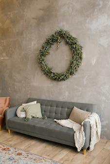 Szara sofa z poduszkami, nad kanapą na ścianie wisi świąteczny wieniec. skandynawski styl w salonie
