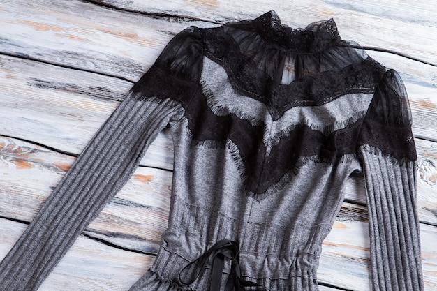 Szara sukienka z czarnymi wstawkami ciemna sukienka na drewnianym tle prezentacja z najwyższej jakości pozycji zam...