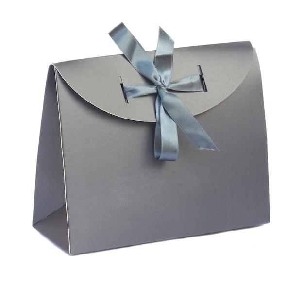 Szara torba na prezent z wstążką na białym tle om białe tło