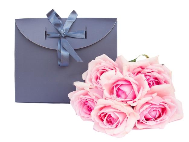 Szara torba na prezent ze świeżych róż na białym tle om białe tło