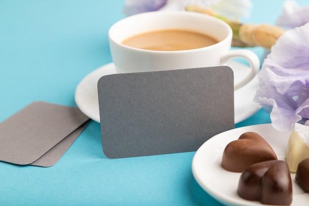 Szara wizytówka z filiżanką cioffee, czekoladowymi cukierkami i kwiatami irysa na niebieskim pastelowym tle